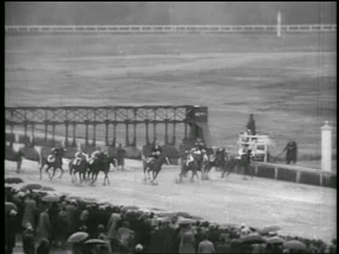 b/w 1935 pan jockeys on horses taking off from starting gate + rounding curve in race - 1935 stock videos & royalty-free footage