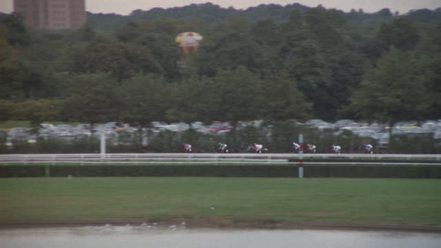 vidéos et rushes de jockeys race horses around a race track in new york city, new york. - animaux au travail