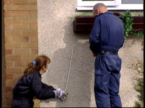 boy arrested itn scotland midlothian ext police officer tilt up pull focus forensic officers outside house of teenage boy arrested on suspicion of... - window box stock videos & royalty-free footage