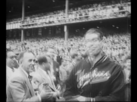 Joe DiMaggio exits dugout at Yankee Stadium wearing baseball jacket over his uniform as officials and crowd in stands applaud / crowd rises to its...