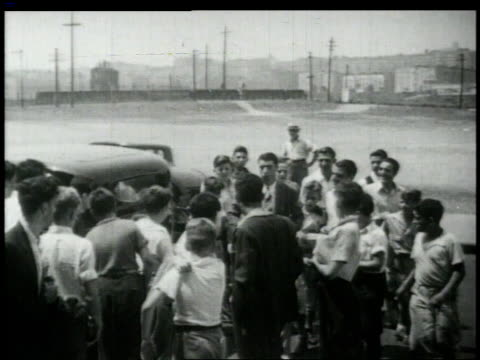 stockvideo's en b-roll-footage met joe dimaggio leaving car swamped by fans / united states - 1949