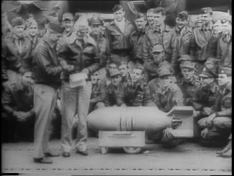 stockvideo's en b-roll-footage met joe james custer at his typewriter outlines doolittle raid plans / animated map / a bomb is rolled on deck, close-up / soldiers pose looking at bomb... - aan elkaar bevestigd