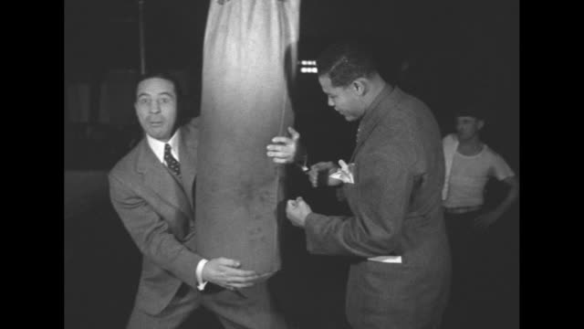 joe louis and max baer, both wearing suits, joke around with punching bag in boxing gym / louis and baer joke around with free weights and laugh /... - pesi massimi video stock e b–roll