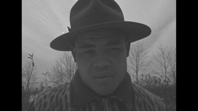 joe louis, wearing hat and animal print jacket, shovels snow on roadside / louis in hat and jacket / trainer wipes down boxer al mccoy in boxing ring... - 格闘技リング点の映像素材/bロール