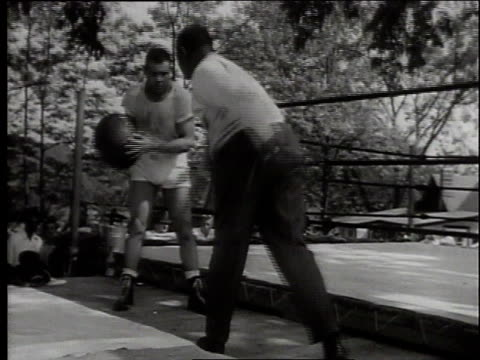 Joe Luis and trainer throwing a medicine ball / crowd watching Joe Louis training / Joe Louis jumping around a boxing ring