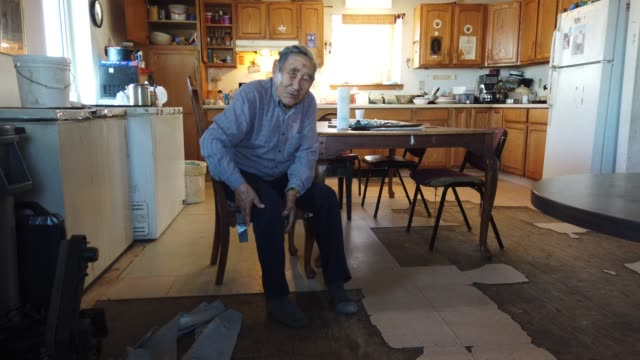 joe swan sits in his home on september 13, 2019 in kivalina, alaska. mr. swan was a grave digger and noticed about 20 years ago that the permafrost... - アラスカ点の映像素材/bロール