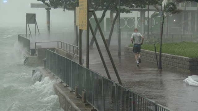 a jogger braves strong wind and blowing spray as typhoon hato hits hong kong on 23rd august 2017 - atlanta braves stock-videos und b-roll-filmmaterial