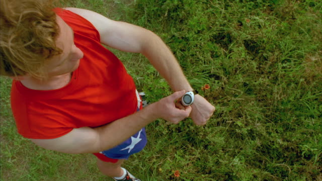 ms zi slo mo jogger checking time in wrist watch / johnson city, texas, usa - johnson city texas stock videos & royalty-free footage