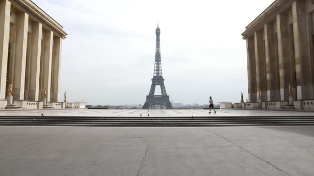 a jogger passes on the trocadero square with the eiffel tower in the background after the head of state ordered the inhabitants to stay at home to... - eiffel tower stock videos & royalty-free footage