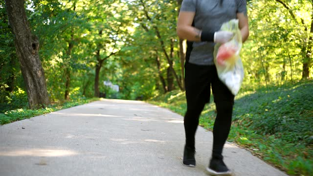 jogger picking up litter in forest - littering stock videos & royalty-free footage
