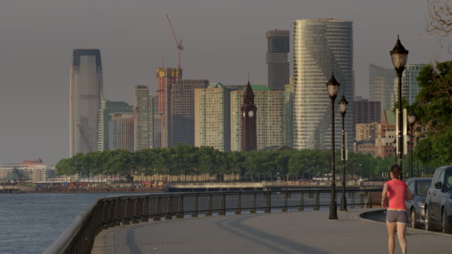 A Jogger Runs Down A Path In Hoboken Nj The Jersey City Skyline Is
