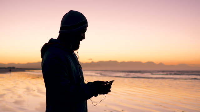 jogger selecting music on a smart phone on a beach at dawn - sports training stock videos & royalty-free footage