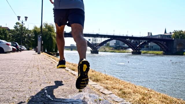 slo mo jogger betreten der pfütze - menschlicher muskel stock-videos und b-roll-filmmaterial