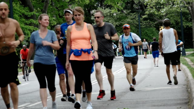 joggers and bicyclist in central park, manhattan, new york city - kopfbedeckung stock-videos und b-roll-filmmaterial