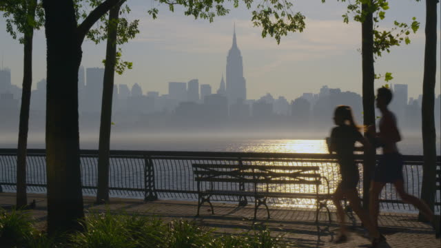 joggers in front of empire state building during sunrise. - ベンチ点の映像素材/bロール