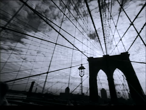stockvideo's en b-roll-footage met b/w pan of joggers on brooklyn bridge to clouds in sky above / nyc - jogster