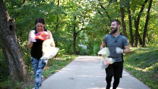 joggers picking up litter in forest - littering stock videos & royalty-free footage