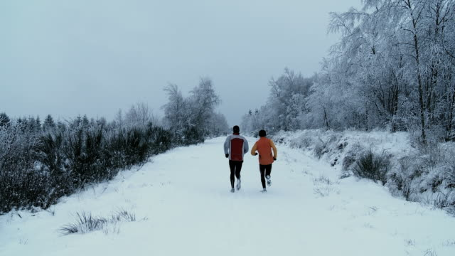 Joggers run on a snow-covered trail in a forest in the Hautes Fagnes area of Belgium.