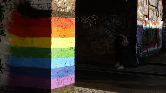 joggers run past rainbow street art in deptford, london - spectrum stock videos & royalty-free footage