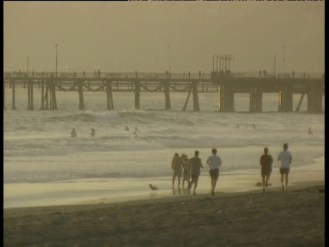 Joggers run through sand on shore at dusk past couple on sand surfers catching waves in sea. Pier in background at dusk Venice Beach
