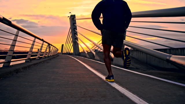 slo mo jogging attraverso un ponte di tramonto - ponte video stock e b–roll