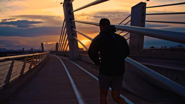 TS Joggen auf der Brücke bei Sonnenuntergang