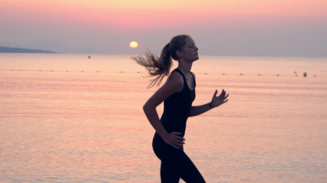 jogging after sunset. beach holiday. close up - tracksuit bottoms stock videos & royalty-free footage