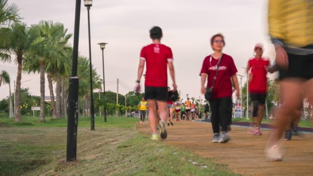 joggen und fahrradfahren in einem park. zeitraffer - menschliche gliedmaßen stock-videos und b-roll-filmmaterial