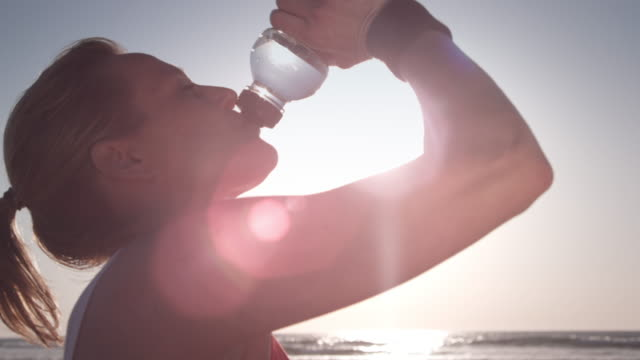 stockvideo's en b-roll-footage met jogging at the beach - drinkwater