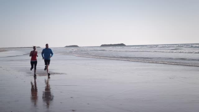 vídeos y material grabado en eventos de stock de hacer jogging en la playa - miembro humano
