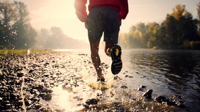 hd super slow-motion: jogging sul fiume - forza video stock e b–roll