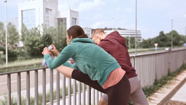 ld jogging couple stretching their legs on a fence - 30 39 years stock videos & royalty-free footage