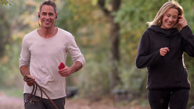 jogging couple with dog in a park on a fall day - close 2-shot - footpath stock videos & royalty-free footage