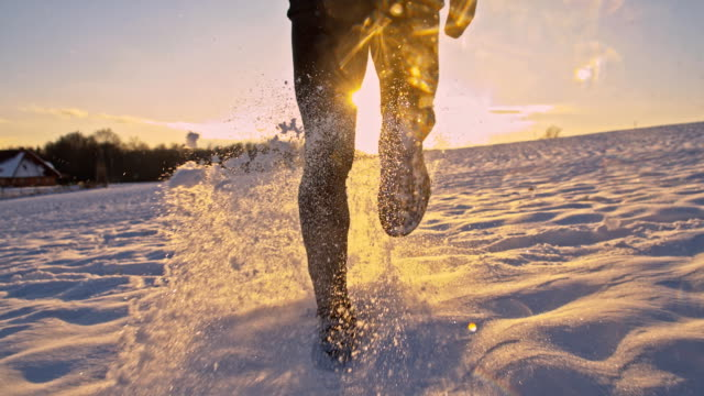 slo mo jogging in the snow - recreational pursuit stock videos & royalty-free footage