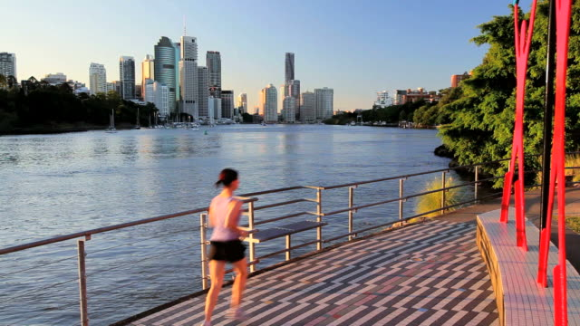 jogging on waterfront passed brisbane city skyline, brisbane, queensland, australia, southern hemisphere - southern hemisphere stock videos & royalty-free footage