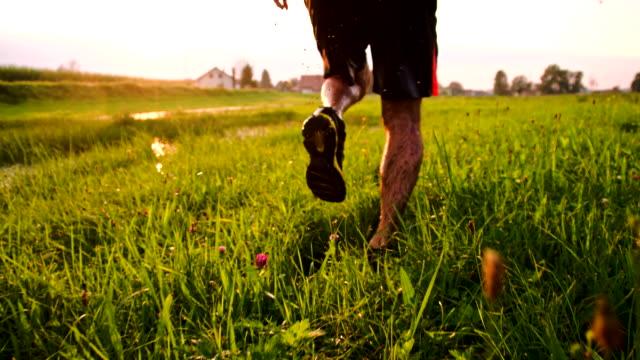 slo mo jogging durch pfützen zu waten im gras - off track laufen stock-videos und b-roll-filmmaterial