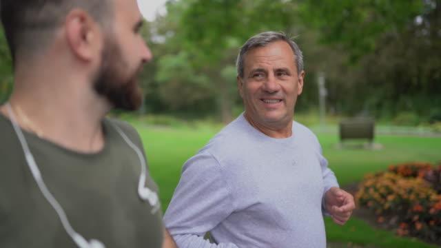 joggen mit sohn im öffentlichen park - in den fünfzigern stock-videos und b-roll-filmmaterial