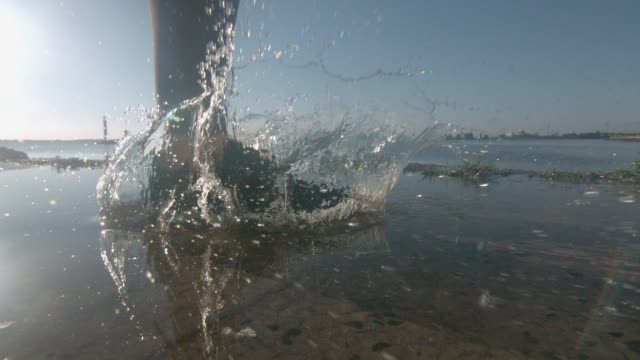 jogging woman stepping in the water with splashes and drops in super slow motion - schuhwerk stock-videos und b-roll-filmmaterial