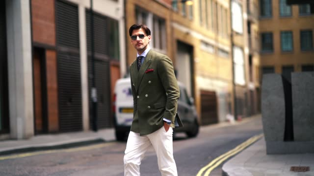Johannes Huebl wears a green khaki blazer jacket sunglasses white pants brown leather shoes a blue shirt a tie during London Fashion Week Men's June...