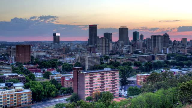 vídeos de stock e filmes b-roll de johannesburg cbd skyline. twilight changing to night with city lights coming on.johannesburg.south africa - joanesburgo