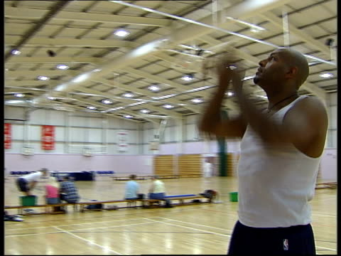 close up john amaechi holding shoe and chatting to man close up basketball ball close up john amaechi putting on shoes amaechi practising and... - youth club stock videos & royalty-free footage
