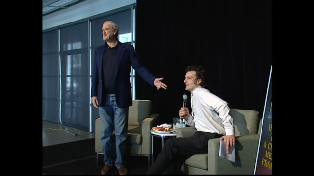 john cleese entering press conference in 2005 and making joke at host oliver driver taking seat before he does - ジョン クリース点の映像素材/bロール