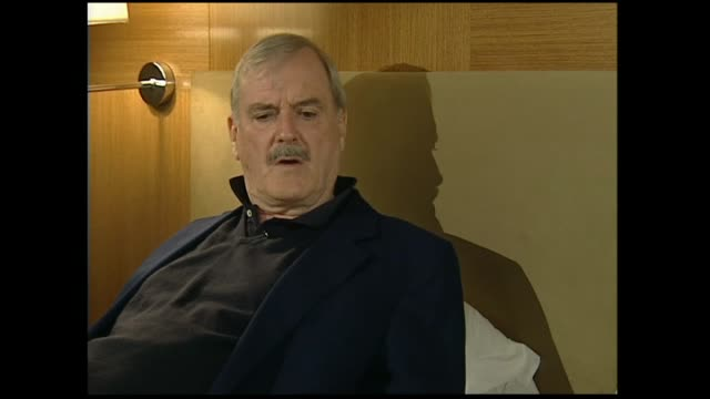 john cleese interviewed on hotel bed in 2005 by host susan wood regarding whether people he meets expect him to be funny all the time - john cleese stock videos & royalty-free footage