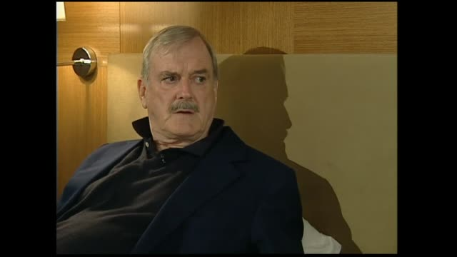 John Cleese interviewed on hotel bed in 2005 by host Susan Wood regarding not thinking too hard for the inspiration for funny ideas
