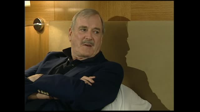 john cleese interviewed on hotel bed in 2005 by host susan wood regarding wanting to be a comedian as it meant he wouldn't have to be a lawyer - john cleese stock videos & royalty-free footage