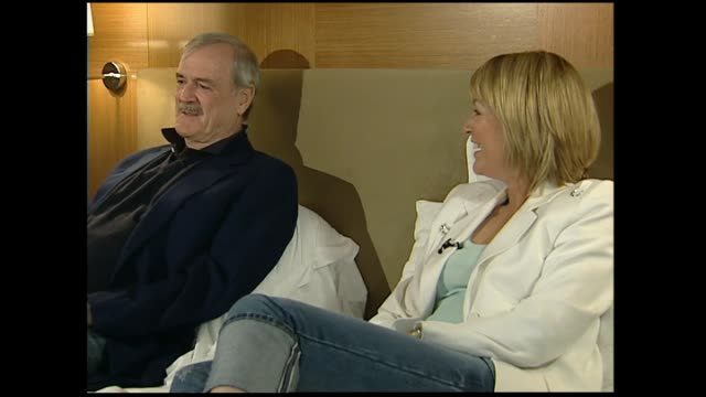 john cleese interviewed on hotel bed in 2005 by host susan wood regarding british newspapers claiming he was a sex symbol in the united states after... - ジョン クリース点の映像素材/bロール