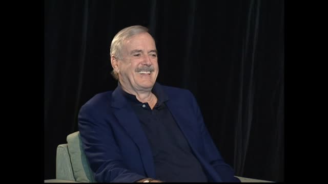 john cleese speaking at press conference in 2005 about choosing projects and joking with host oliver driver about previous visit to dunedin and had... - ジョン クリース点の映像素材/bロール