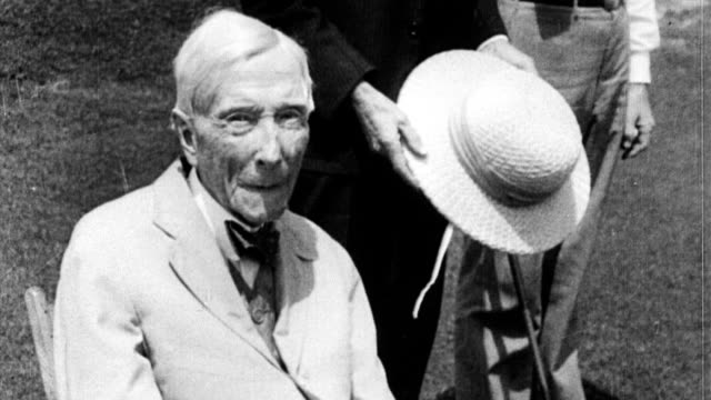 john d rockefeller hitting golf ball at 94 years old and then sitting in a chair - anno 1933 video stock e b–roll