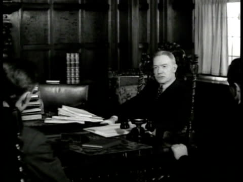 john d rockefeller jr sitting at desk in office talking to man in chair assistant handing him papers ornate chair philanthropist rockefeller center... - rockefeller center video stock e b–roll
