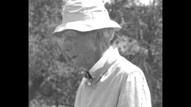 VS John D Rockefeller Sr putts golf ball on the grounds of his estate 'The Casements' in Florida and watches as a female friend putts / CU...